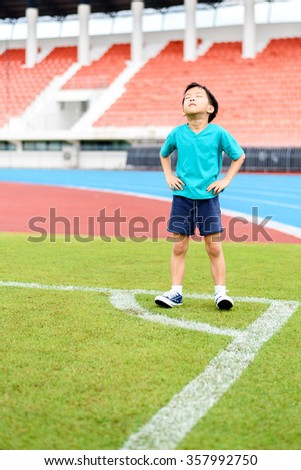 Young Asian boy standing on green football field in stadium during day time and feel relax. - stock photo