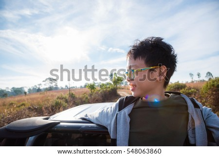 Young asian boy standing on truck and looking field on hill