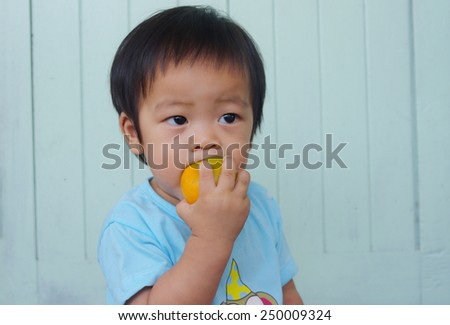 Young Asian boy tries to eat an orange. - stock photo