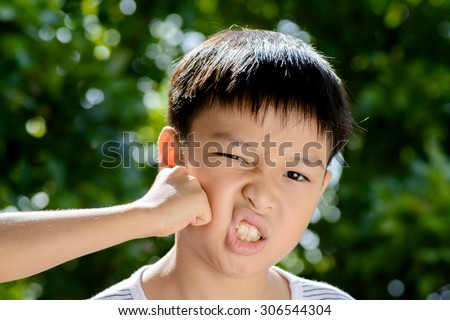 Young asian boy was hit by his brother in front of green bokeh background from tree leaf