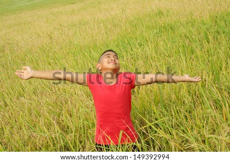 Young asian boy with green rice field background.  - stock photo