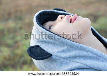 Young asian boy with hooded sweatshirt looking up in the morning light - stock photo