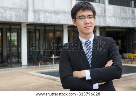 young asian business man cross himself's arm looking straight for conceptual use