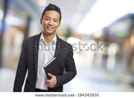 young asian business man holding a book - stock photo