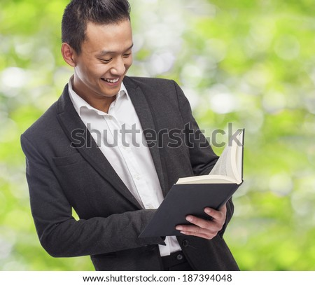young asian business man holding a book