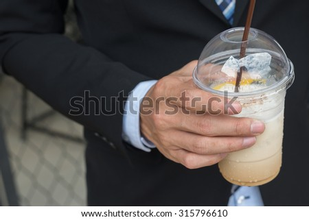 young asian business man holding an ice coffee in his hand - stock photo