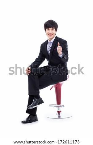 Young Asian business man sitting on the chair and showing thumb isolated on white background.