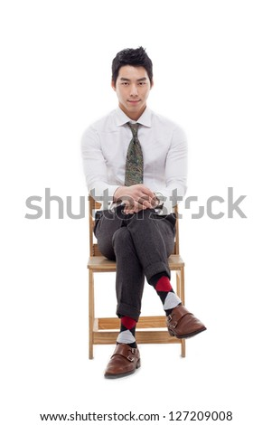 Young Asian business man sitting on the chair isolated on white background. - stock photo