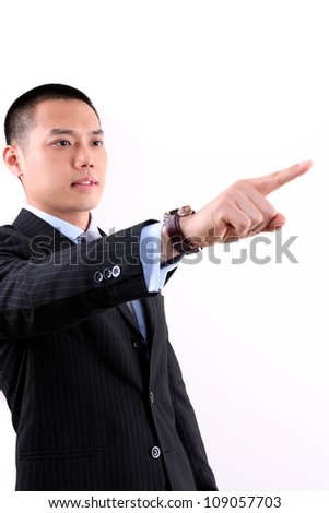 Young asian business man standing on white background and pointing away