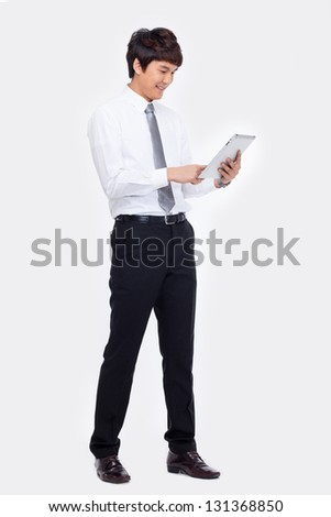 Young Asian business man using a pad PC isolated on white - stock photo