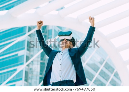 Young Asian business man wearing VR glasses goggles arms open feeling freedom or success with office building background
