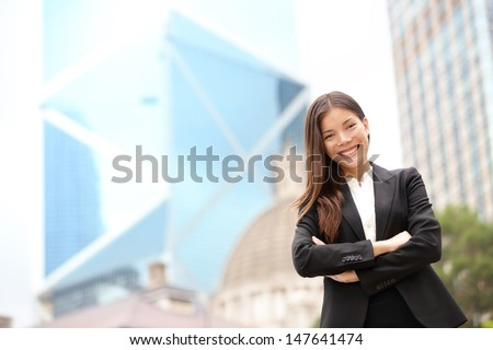 Young Asian business people business woman portrait outside. Businesswoman standing proud looking at camera in suit. Multiracial Chinese Asian / Caucasian female professional in central Hong Kong. - stock photo