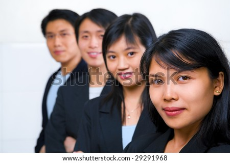Young Asian business people line up, with focus on the front woman (South East Asian woman)