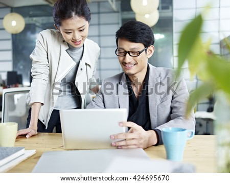 young asian business people sitting at desk working together using laptop computer. - stock photo