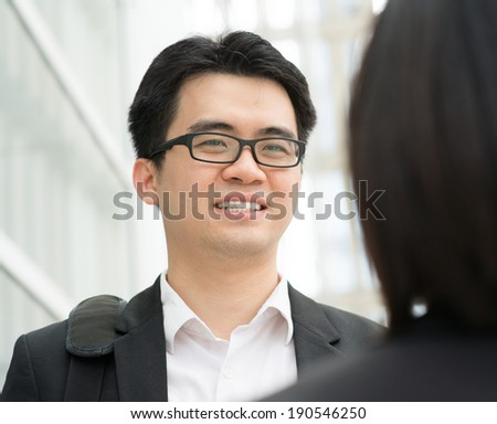 Young Asian business team having discussion over office. - stock photo