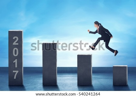 Young asian business woman jumping to the chart toward numbers 2017. New Year Concept.