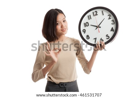 Young Asian business woman show OK with a clock  isolated on white background .