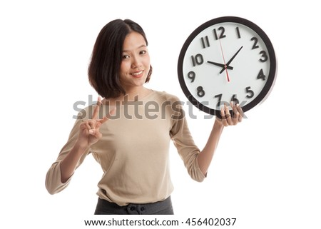 Young Asian business woman show victory sign with a clock  isolated on white background