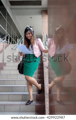 Young Asian business woman smiling, reading a letter, walking at an outdoor office environment