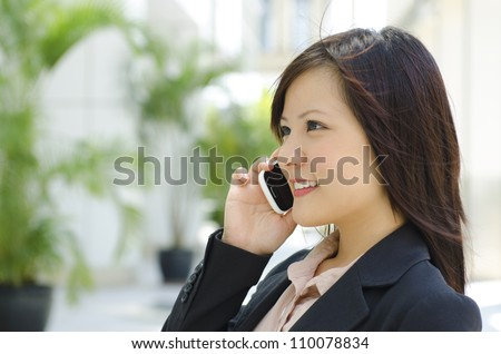 Young Asian business woman talking phone outside modern building - stock photo