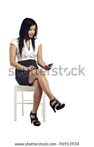Young asian business woman using her mobile on white background - Sitting on chair - stock photo