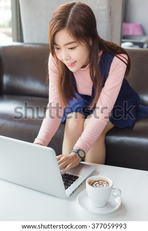 Young asian business woman using laptop outdoors.