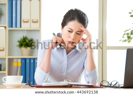 Young asian business woman writing with headache in office