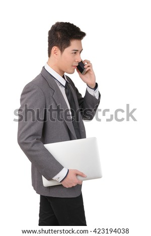 Young asian businessman answering smart phone and hold with laptop computer isolated over white background. Vertical shot.