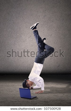Young asian businessman breakdancing with laptop. shot over grey background - stock photo