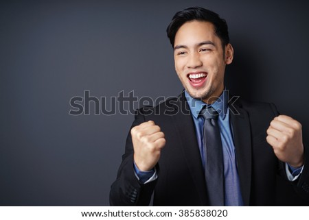 Young Asian businessman cheering in jubilation raising his fists in the air as he celebrates his success - stock photo