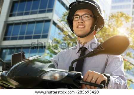 Young asian businessman commuting to job in the morning. The man rides a motorcycle scooter with white helmet and looks away - stock photo