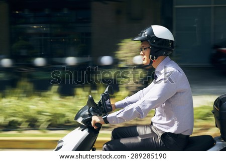 Young asian businessman commuting to job. The man rides a motorcycle with white helmet. Motion blurred background - stock photo
