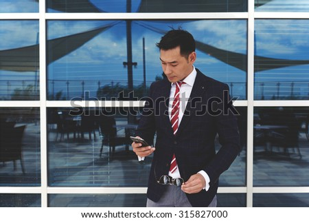 Young asian businessman holding his mobile phone while standing at office building window outdoors, successful man entrepreneur dressed in stylish luxury clothes using cell telephone during work break - stock photo