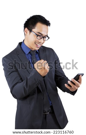 Young asian businessman holding smartphone and expressing his success - stock photo