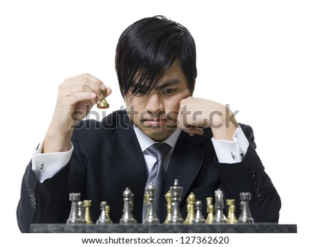Young asian businessman playing chess - stock photo