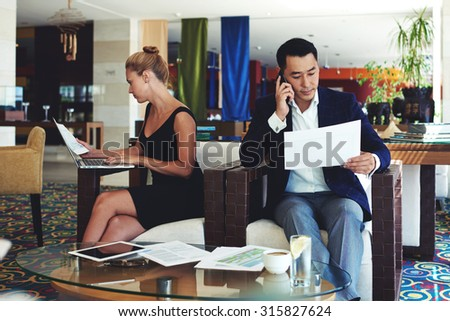 Young asian businessman read monthly report on the papers during telephone conversation, intelligent woman examines documents while work on net-book, successful male and female preparing for briefing - stock photo