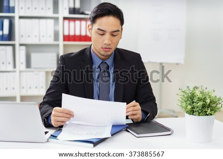 Young Asian businessman sitting at his desk in the office proof reading a report making notes with a pen as her reads through it