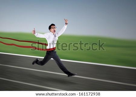 Young asian businessman winning a business race outdoor - stock photo