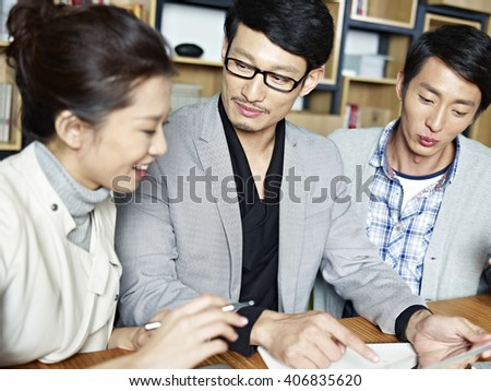 young asian businesspeople working together in office using tablet computer. - stock photo