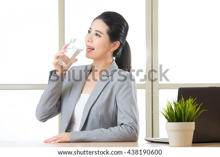 Young asian businesswoman drinking glass of water in office - stock photo