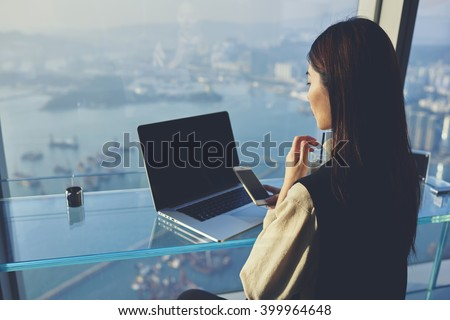 Young Asian businesswoman is holding mobile phone with blank display, while is sitting in skyscraper building at the table with open laptop computer with empty copy space screen for your advertising - stock photo