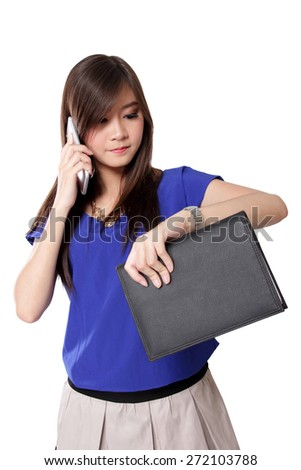 Young Asian businesswoman looking at her wrist watch while talking on mobile phone, isolated on white background - stock photo
