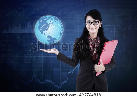 Young Asian businesswoman smiling at the camera while holding a globe with social network icon. Elements of this image furnished by NASA