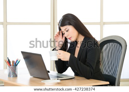 Young Asian businesswoman thinking and drinking coffee on the desk in the office - stock photo