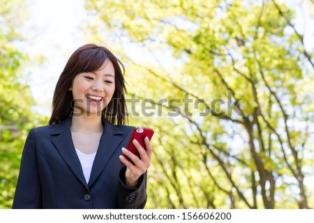 young asian businesswoman using smart phone in the park - stock photo