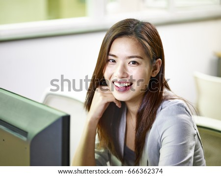young asian businesswoman working in office looking at camera smiling.