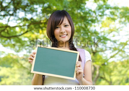 Young Asian college girl holding a blackboard outdoor, green park - stock photo