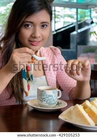 Young Asian college girl student sitting on campus cafe, breakfast with coffee and sandwish, smile, feel relax and enjoy