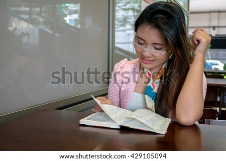 Young Asian college girl student sitting on campus cafe, smile and writing notebook - stock photo
