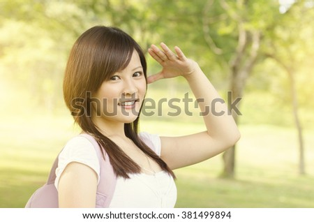 Young Asian college girl student standing on campus lawn, hand shielding and smiling. - stock photo